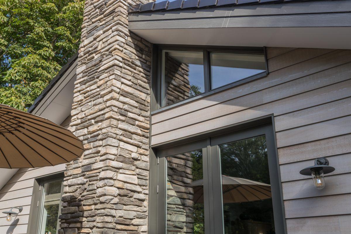 De woning is gebouwd in houtskeletbouw. De dampopen buitenbetimmering in de duurzame houtsoort Western Red Cedar (WRC), wat vooraf vergrijsd is. Rondom het huis is nagemaakte Geopietra steen gebruikt.