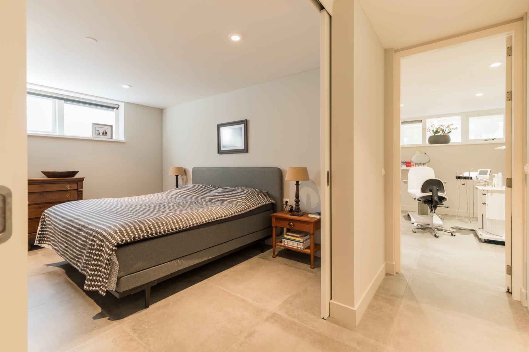 Slaapruimte en praktijkruimte in het souterrain, met veel licht door de hoge ramen
